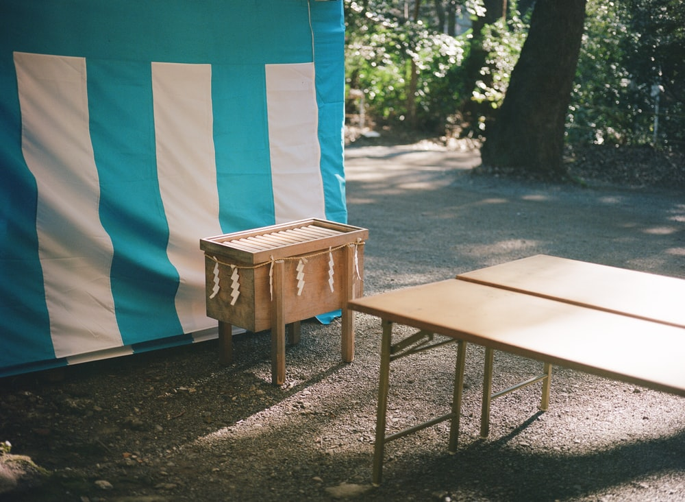brown wooden table near blue and white tent