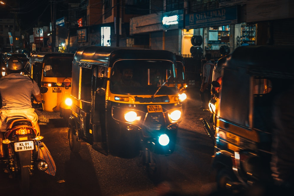 black and yellow auto rickshaw on road during nighttime