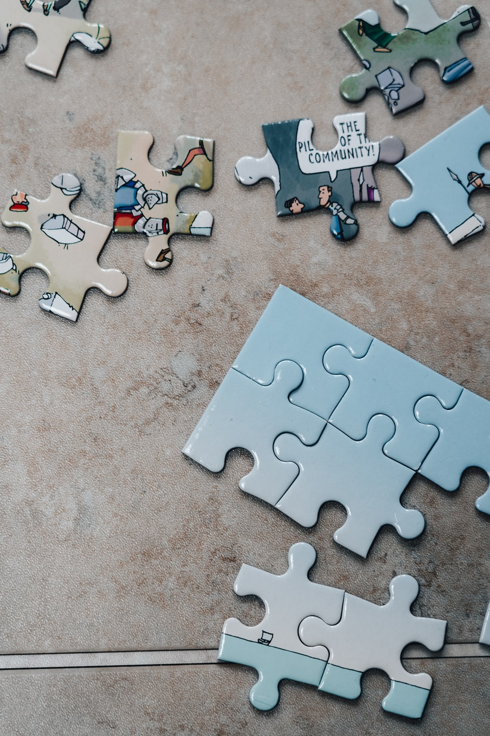 white jigsaw puzzle pieces on brown marble table
