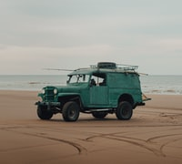 green suv on brown sand beach during daytime