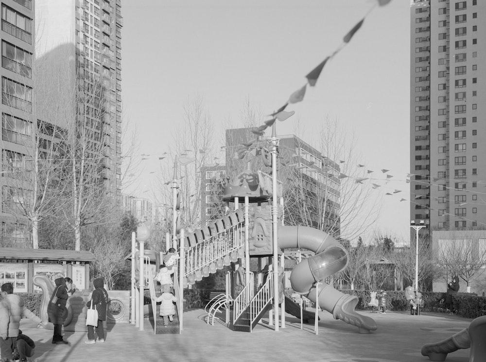 grayscale photo of people walking on street near buildings