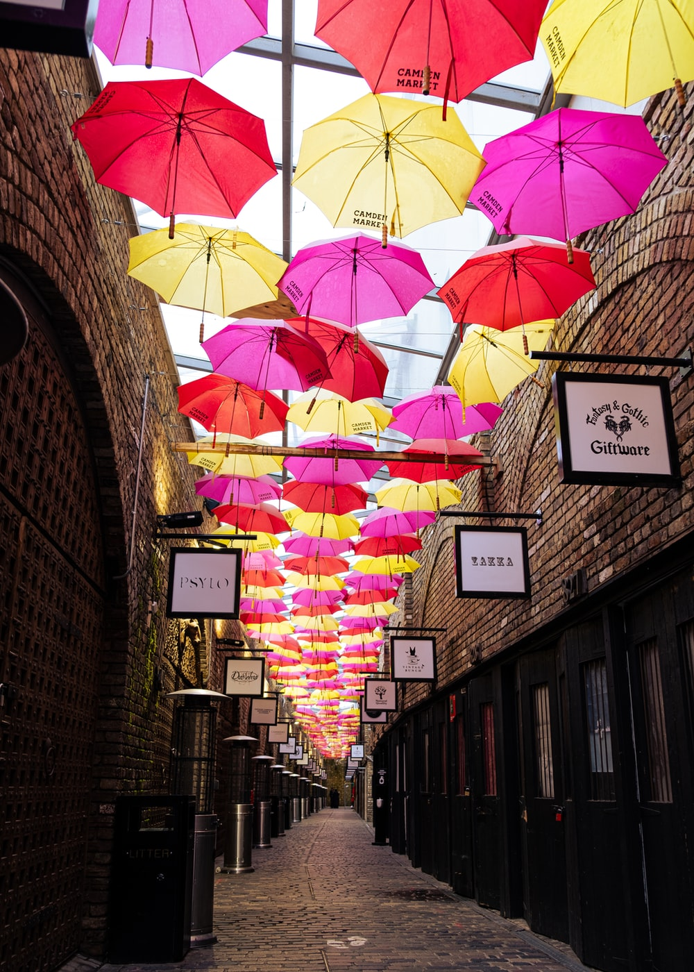 assorted umbrellas hanging on brown brick wall