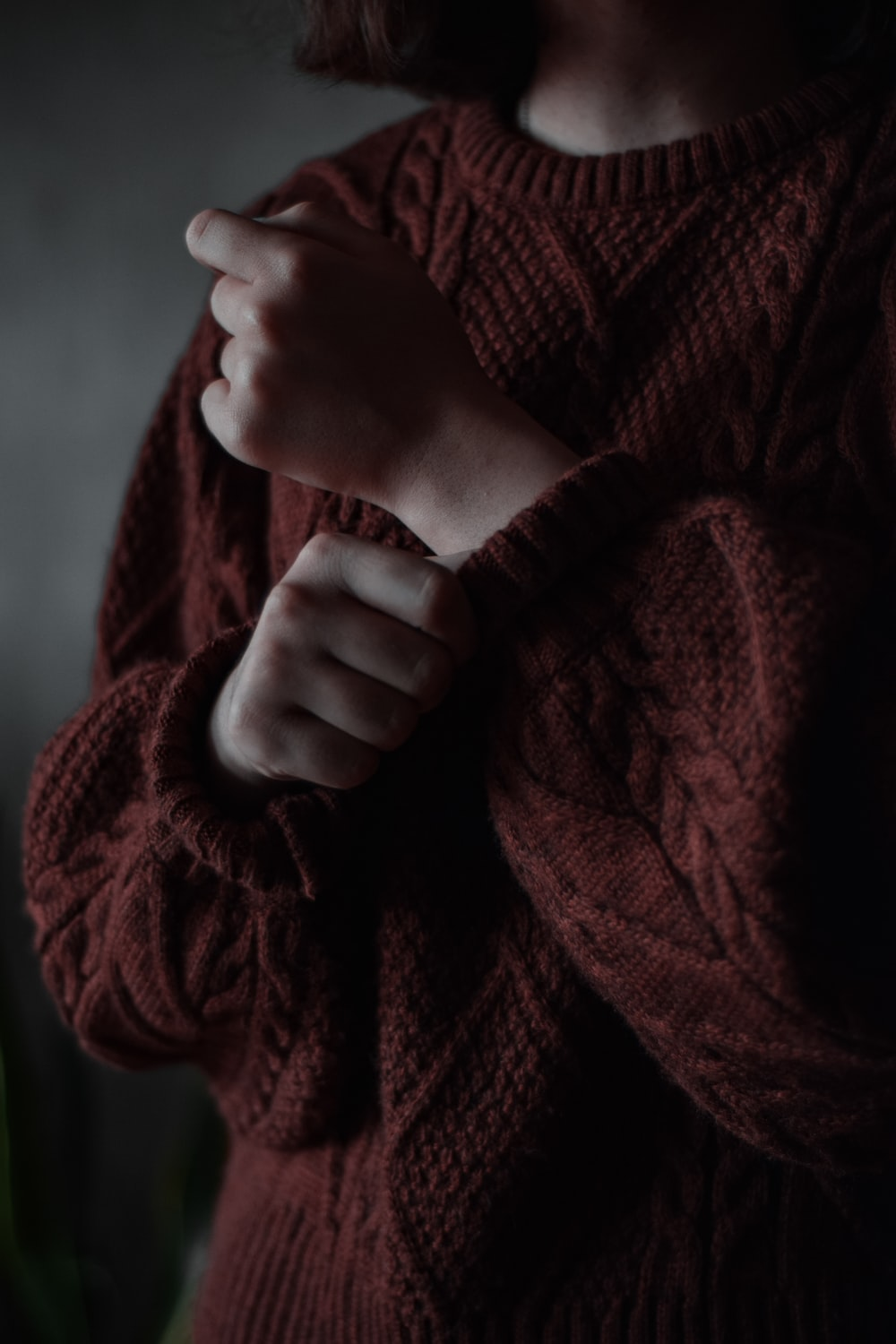person holding red knit textile