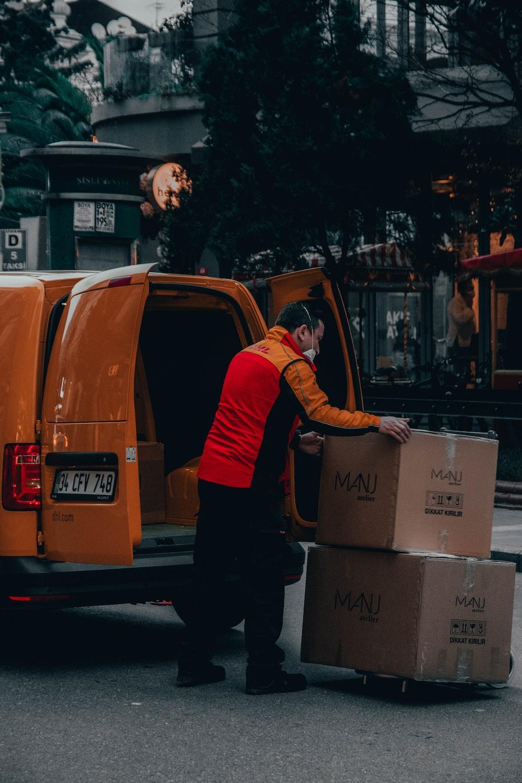 man in red jacket standing beside orange van during daytime