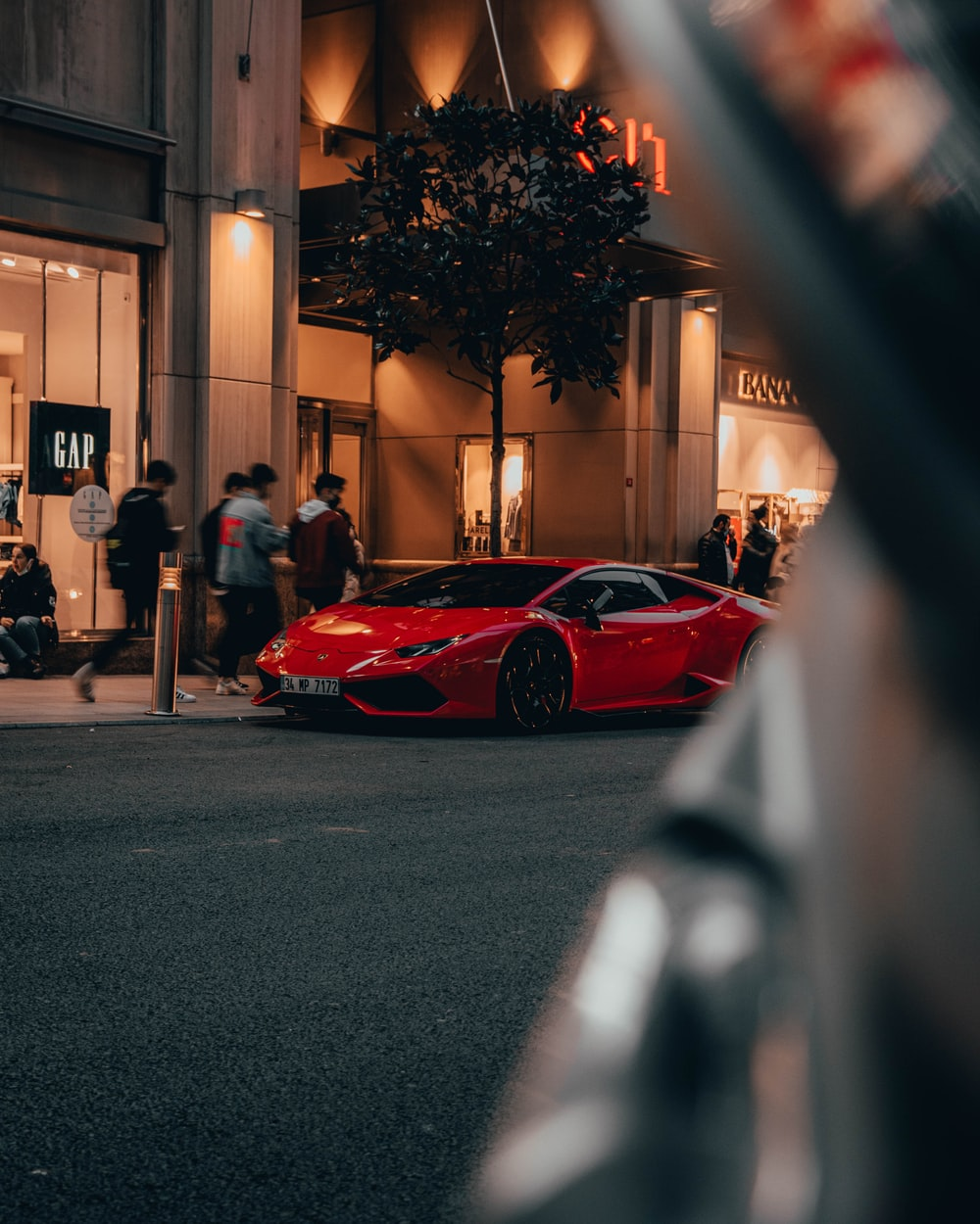 red car parked on sidewalk during night time
