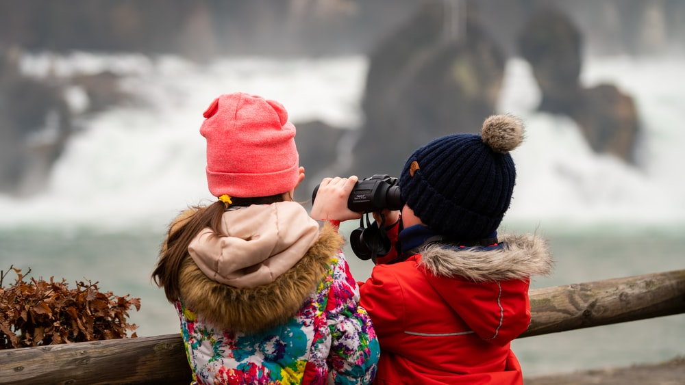 woman in red knit cap and brown jacket holding black dslr camera