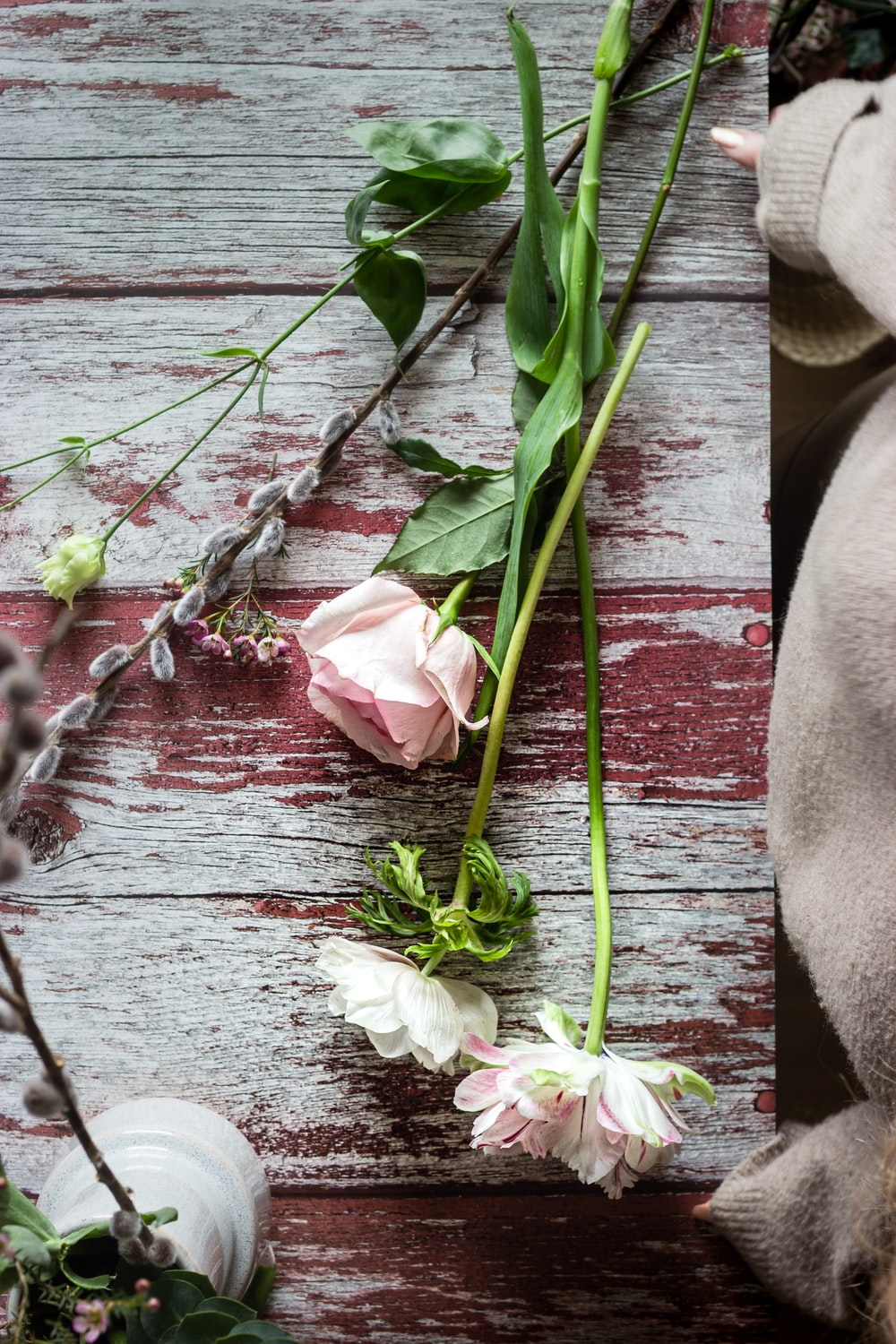 white and pink flowers on brown wooden surface