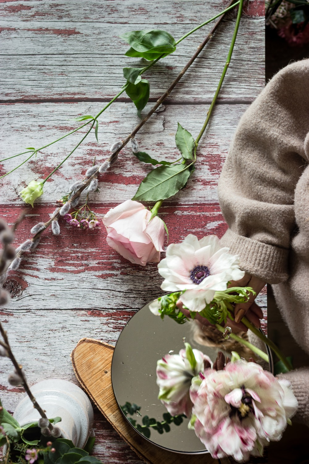pink and white flower on brown wooden table