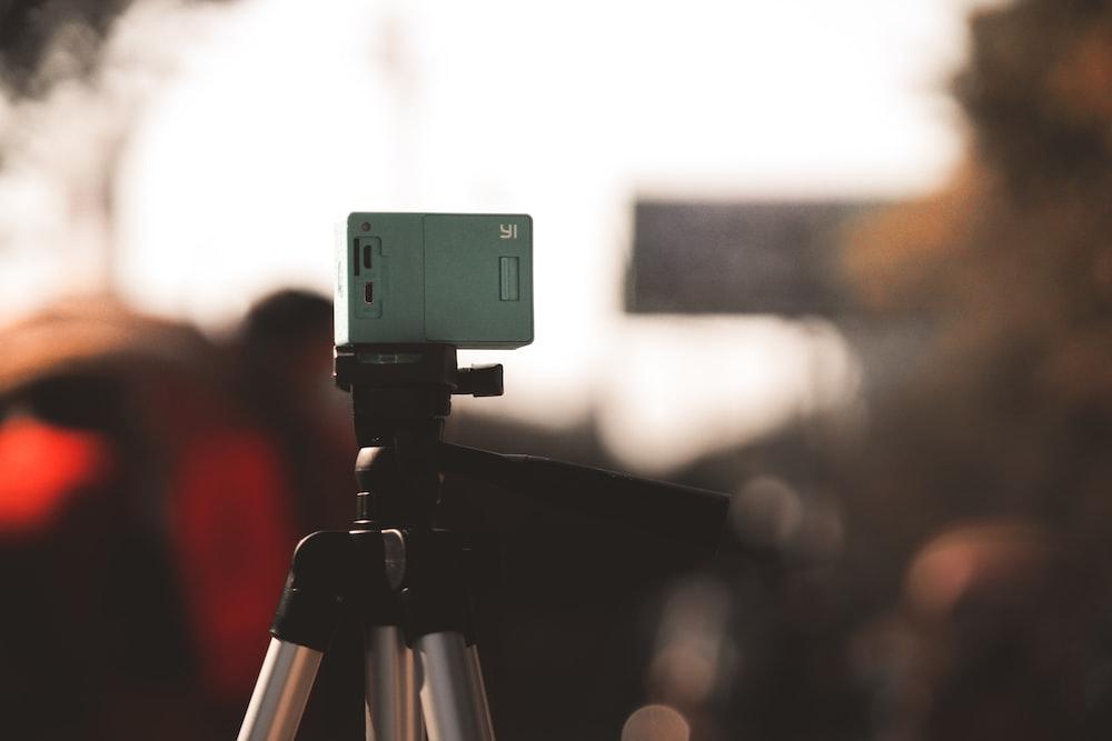 green and black camera on tripod