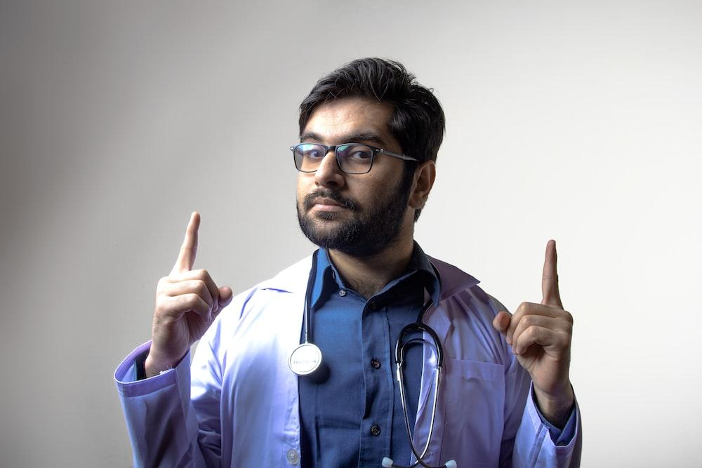 man in blue scrub shirt wearing black framed eyeglasses