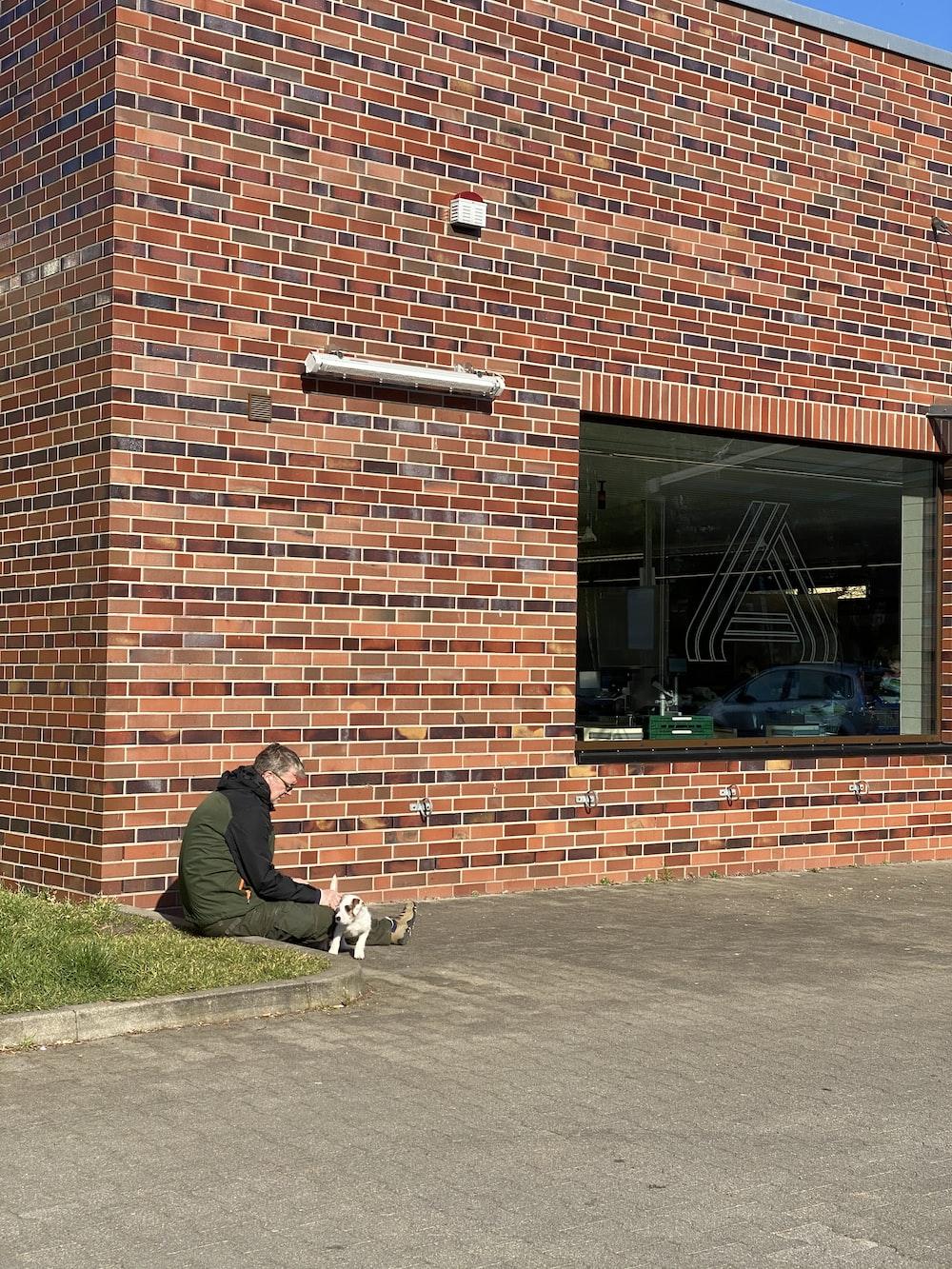man in black jacket and white pants sitting on sidewalk during daytime