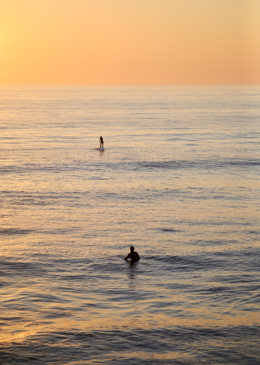 2 people swimming on sea during sunset