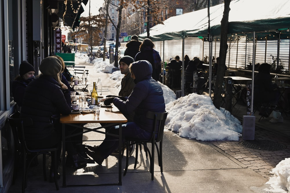 people sitting on chair in front of table covered with snow during daytime