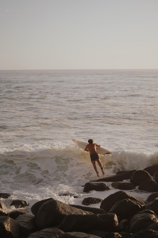 woman in black bikini standing on rock near sea during daytime