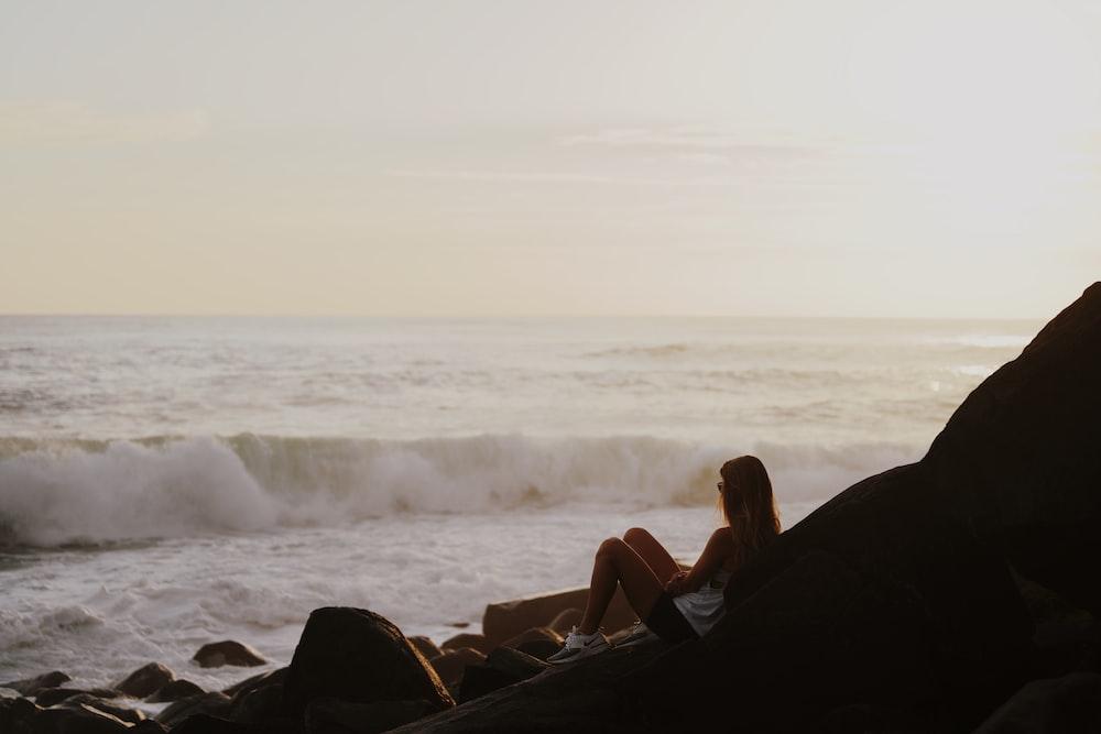 woman in black tank top sitting on rock near sea during daytime