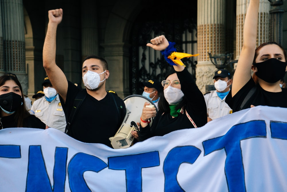 man in black vest wearing white mask holding white and blue flag