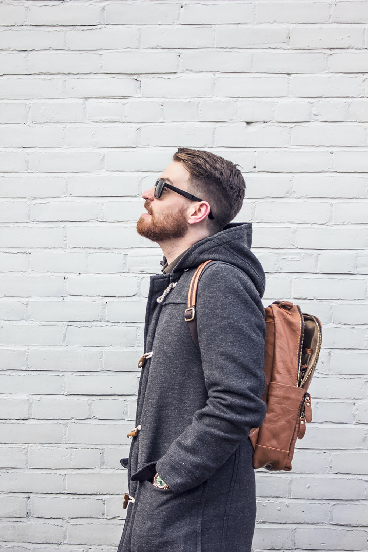 man in black jacket wearing black framed eyeglasses