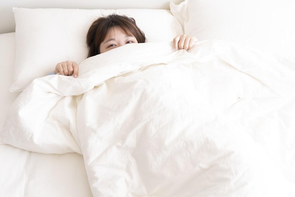 girl lying on white bed