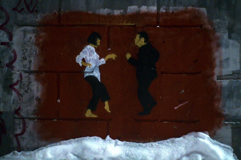man in white jacket and black pants playing on snow