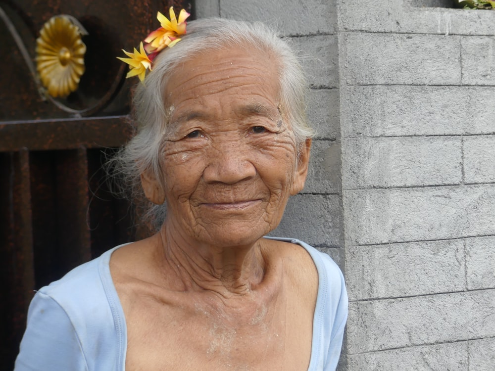 woman in white tank top with yellow flower on her ear