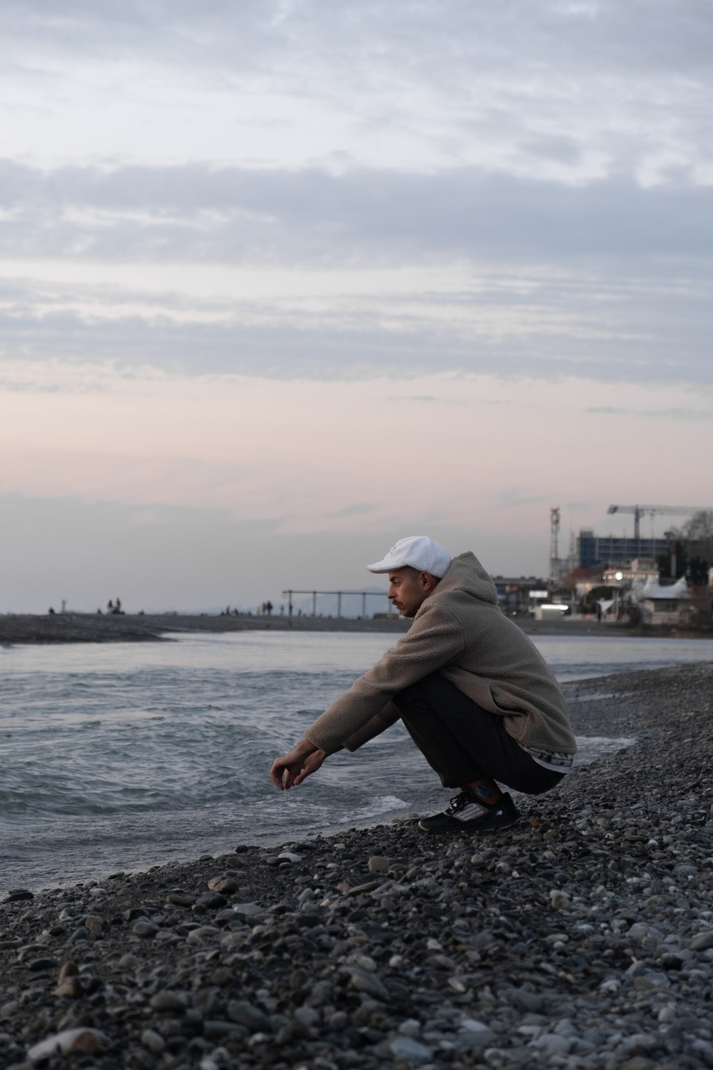man in gray hoodie and black pants sitting on rocky shore during daytime