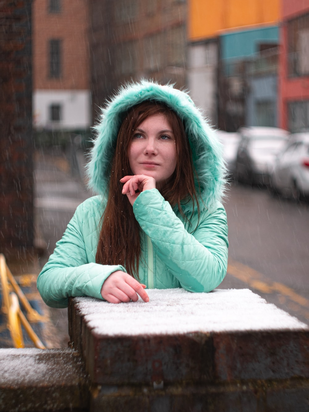 woman in teal hoodie sitting on brown wooden bench during daytime