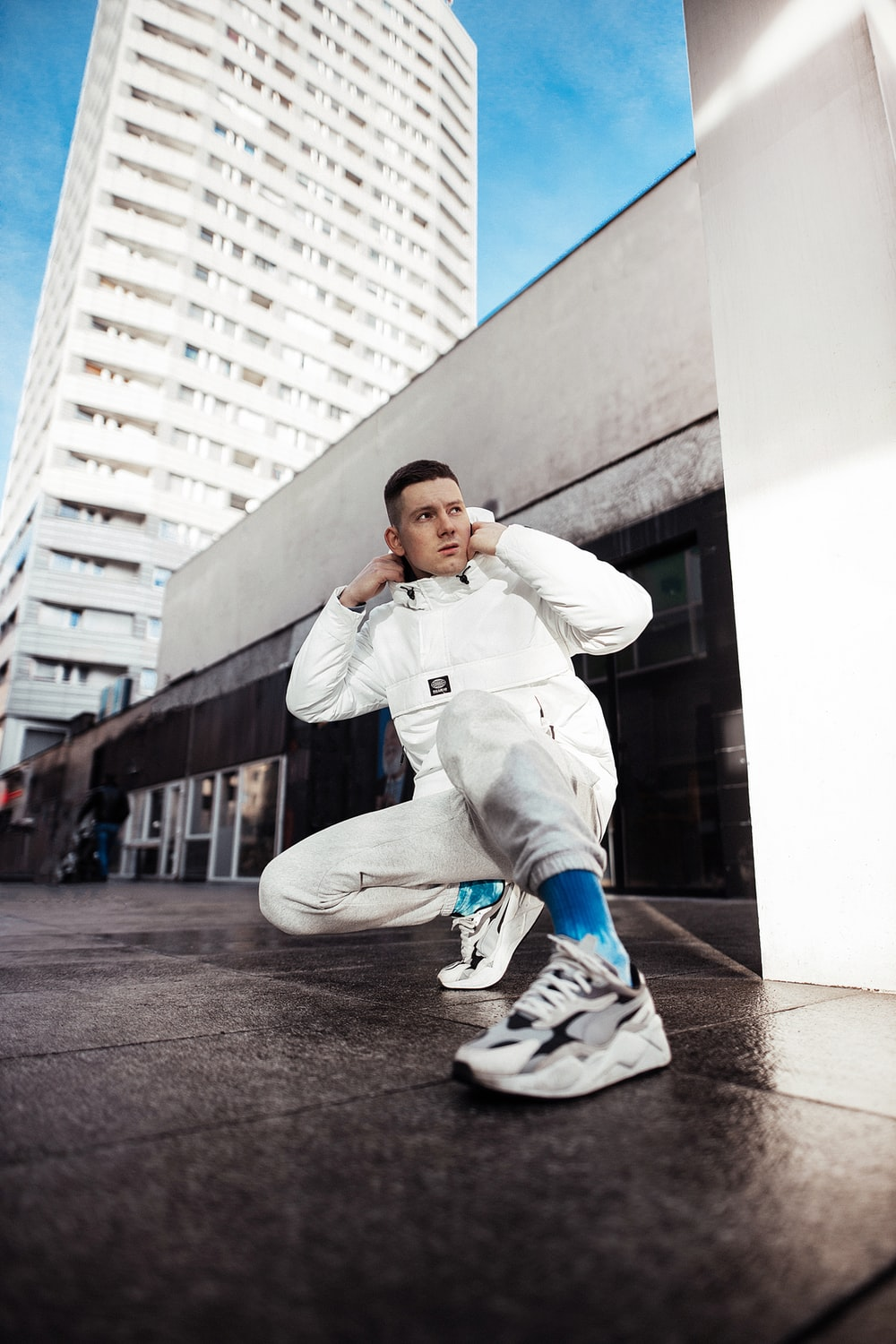 boy in white hoodie and blue pants sitting on gray concrete floor during daytime