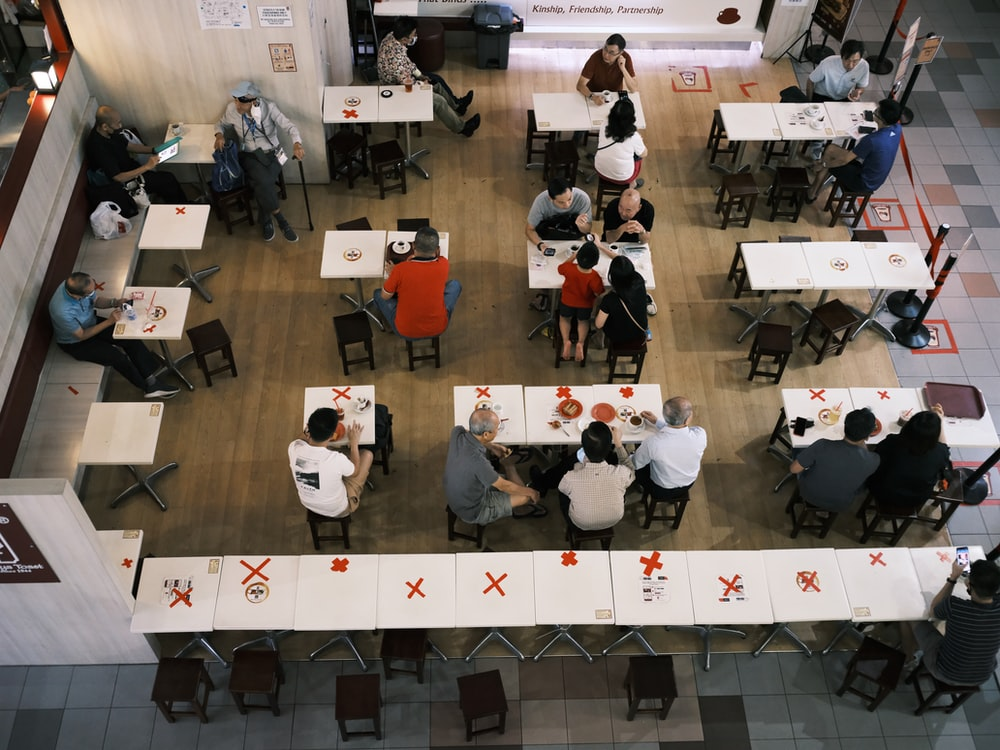 people in a room with white tables and chairs