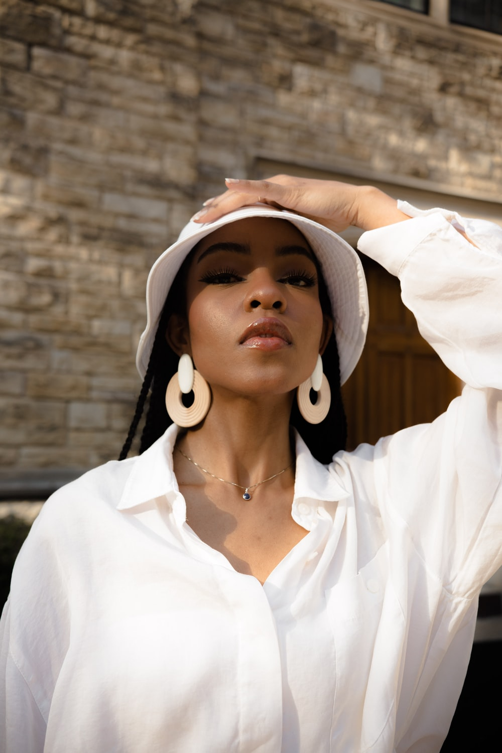 woman in white button up shirt wearing white and brown hat