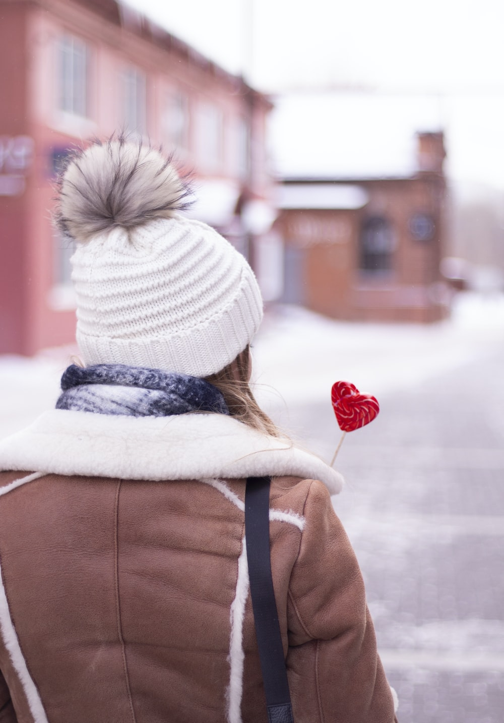 person in brown jacket and white knit cap holding red heart balloon
