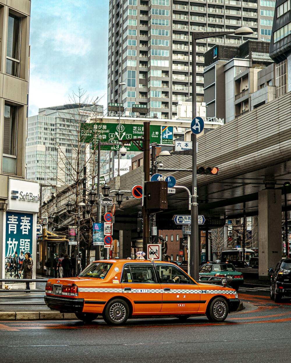 red sedan on road near buildings during daytime