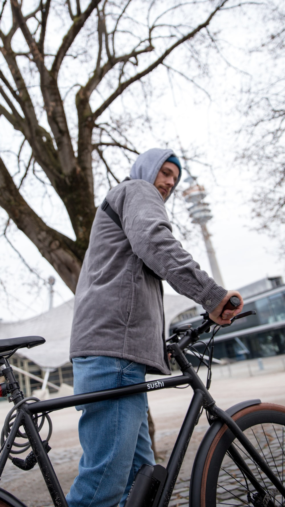 man in gray hoodie and blue denim jeans riding on bicycle during daytime