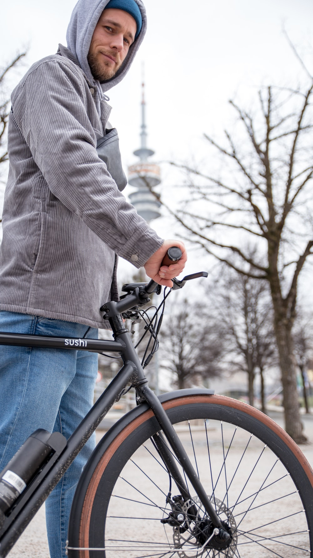 person in gray sweater and blue denim jeans riding black bicycle