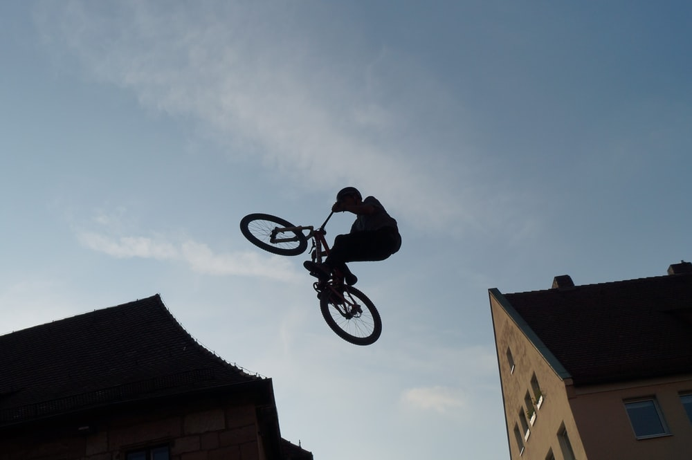 silhouette of man riding bicycle on mid air during daytime