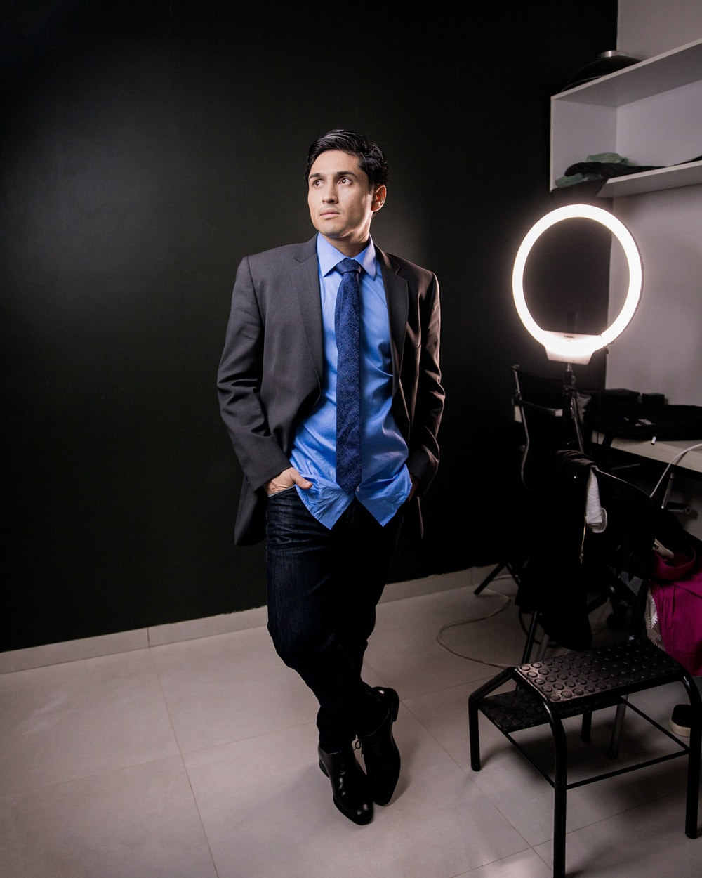 man in black suit standing near black table