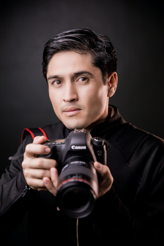 man in black leather jacket holding black nikon dslr camera