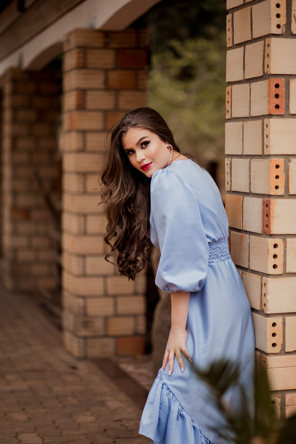 woman in blue dress standing beside brown brick wall during daytime