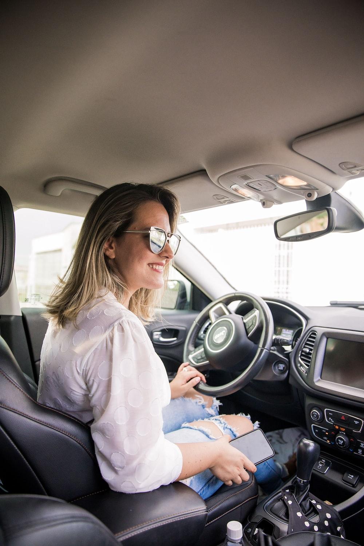 woman in white long sleeve shirt driving car