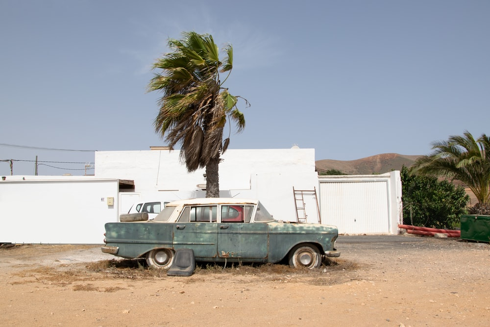 green and white vintage car parked beside white concrete building during daytime