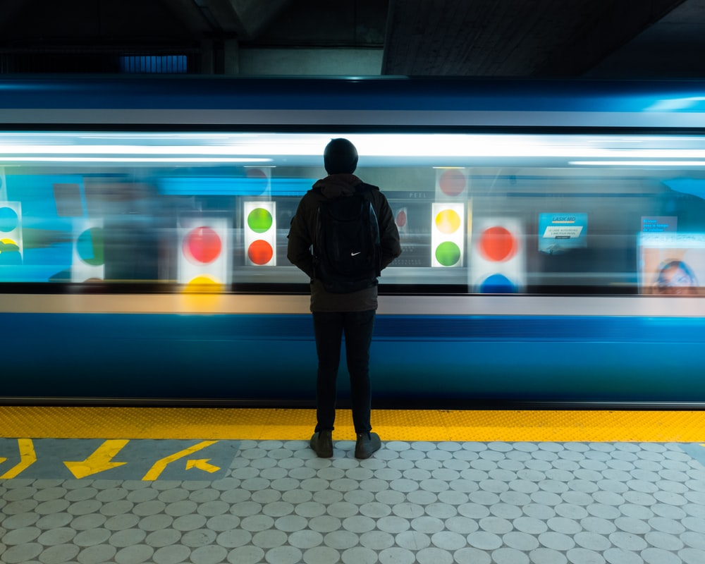 man in black jacket standing on train station