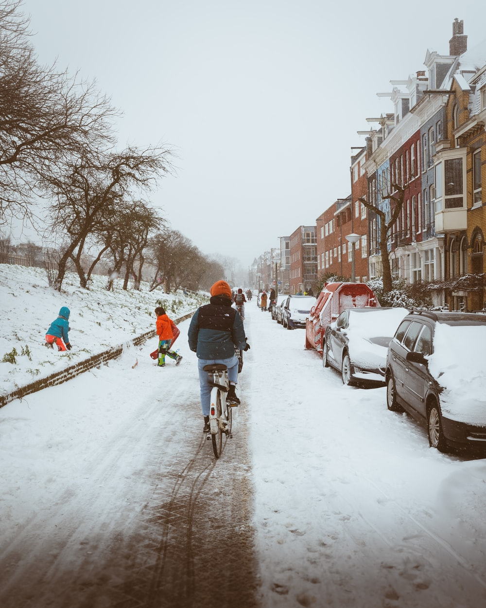 man in red jacket riding bicycle on snow covered road during daytime