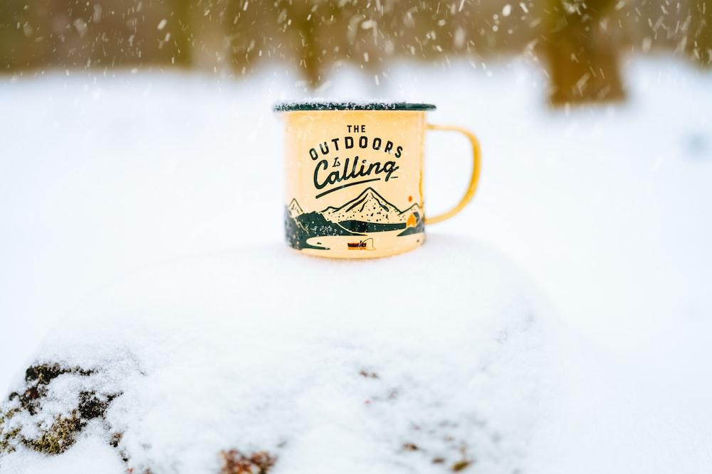 white and yellow ceramic mug on white snow