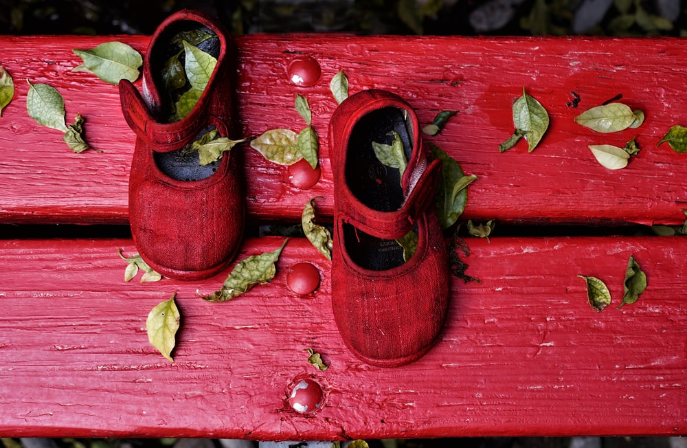 brown and black boots on red wooden surface