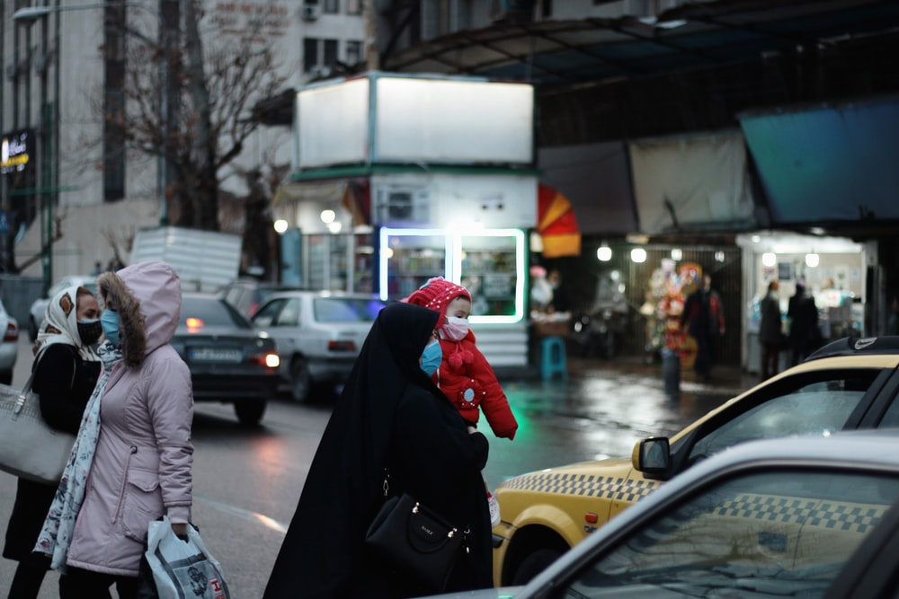 man in black hoodie and red knit cap walking on street during daytime