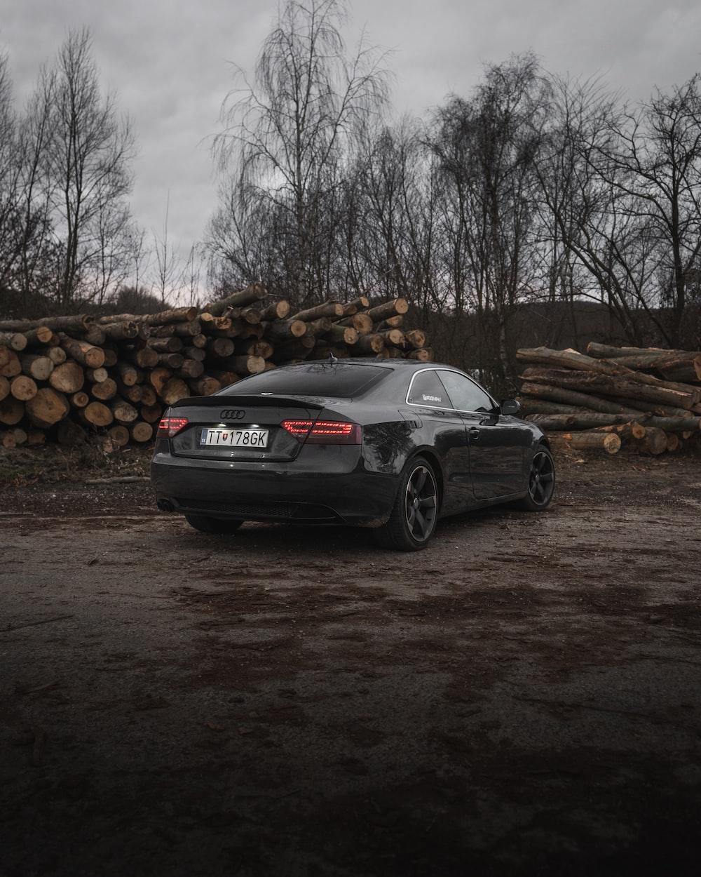 black sedan parked near pile of woods during daytime