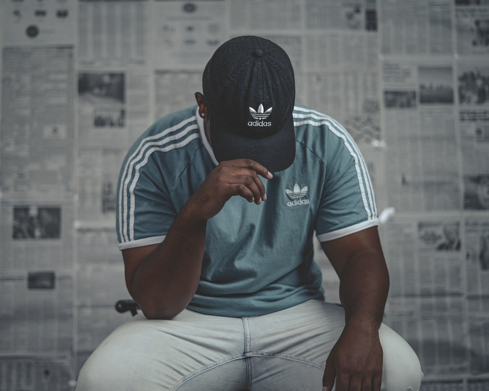 man in white and black adidas crew neck t-shirt and gray pants sitting on white