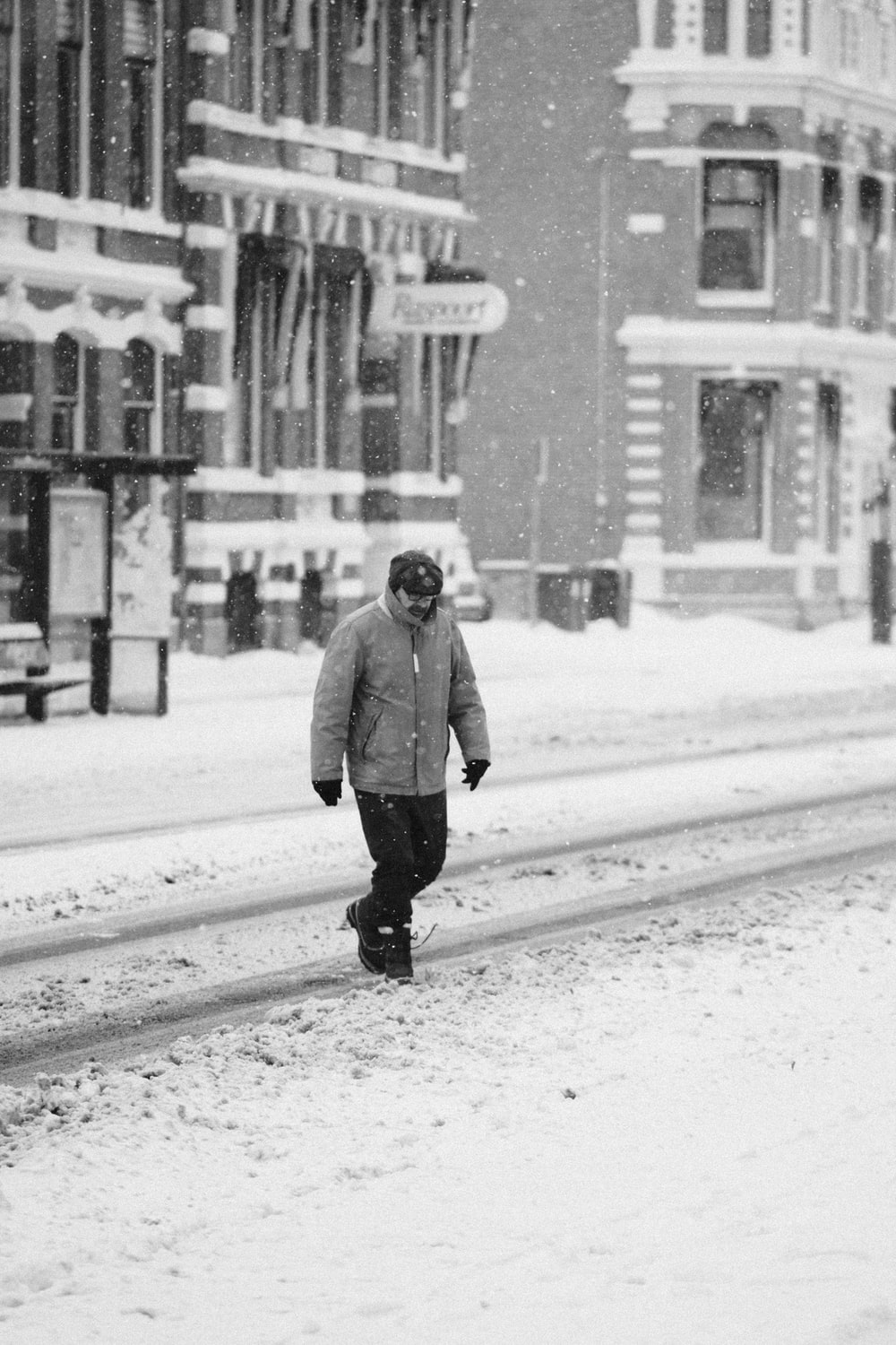 man in gray coat standing on snow covered ground