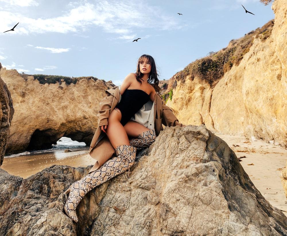 woman in black tank top sitting on brown rock during daytime