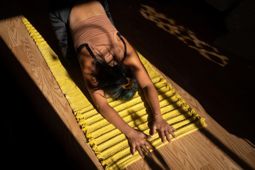 woman in black tank top lying on yellow hammock