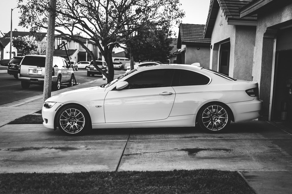 grayscale photo of coupe parked near tree